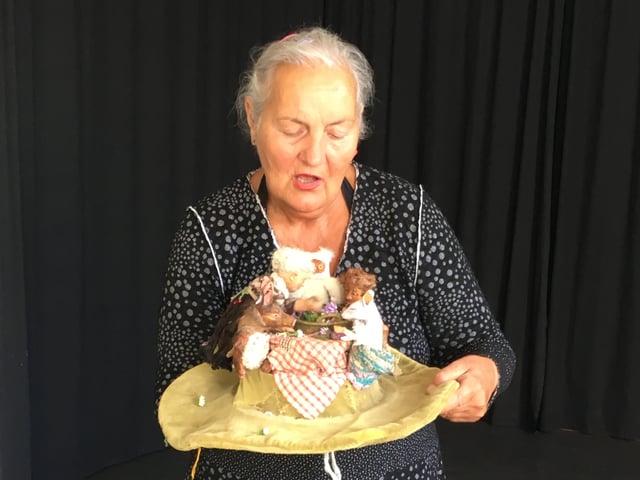 Margrit Gysin hält einen Hut in der Hand. Darauf spielt sie mit kleinen Puppen