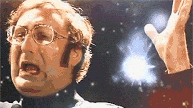 Ein Mann signalisiert Erstaunen vor Feuerwerk.