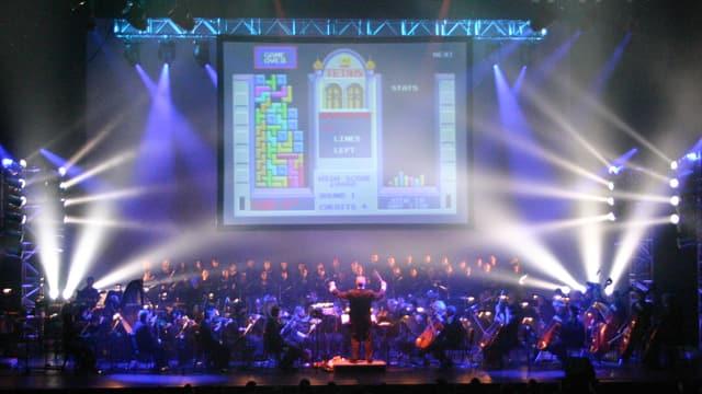 """Auf einer Bühne spielt ein Orchester, im Hintergrund eine Leinwand auf der das Spiel """"Tetris"""" zu sehen,"""