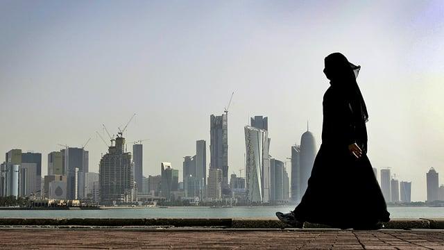 Verschleierte Frau spaziert vor der Skyline in Doha.
