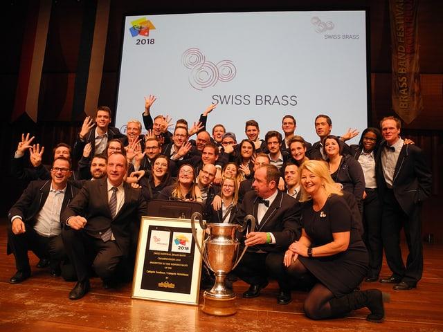 Eine Gruppe Menschen mit Diplom und Siegerpokal.