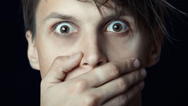 Ein Mann hält sich geschockt die Hand vor den Mund.
