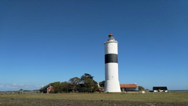 Ein schwarz-weisser Leuchtturm unter blauem Himmel.