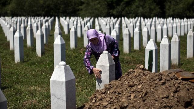 Eine muslimische Frau pflegt einen Grabstein auf einem Friedhof.