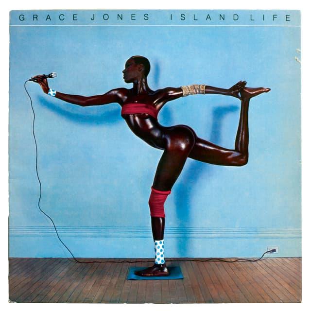 Grace Joney balanciert auf einem Bein und hält ein Mikrofon.