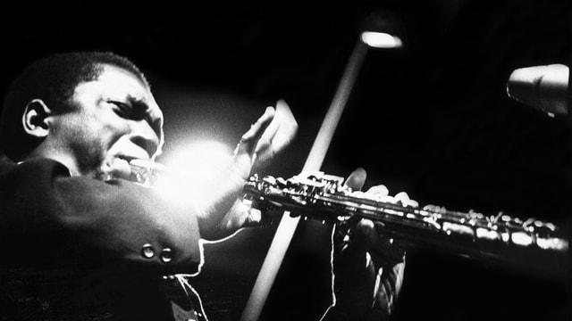 Schwarz-WEiss-Foto: Ein schwarzer Mann spielt Saxohon, die Augen zusammengekniffen, voller Gefühl.