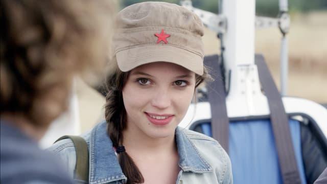 Eine junge Fraum mit einer Mütze mit einem Stern drauf, sie trägt eine Jeansjacke.