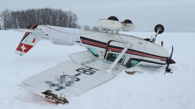 Das Flugzeug liegt im Schnee auf dem Dach und sieht ein bisschen skurill aus...