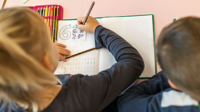 Ein Schüler schreibt Zahlen in sein Heft