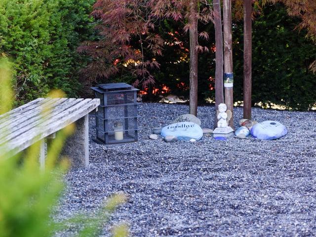 Tierfriedhof: Eine Bank, Bäume und bemalte Steine auf dem Boden