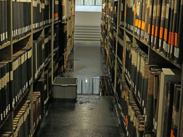 Archivregale, dazwischen eine Wasserpfütze