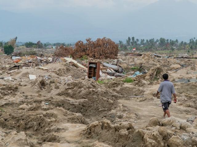 Mann schreitet durch eine zerstörte Landschaft.