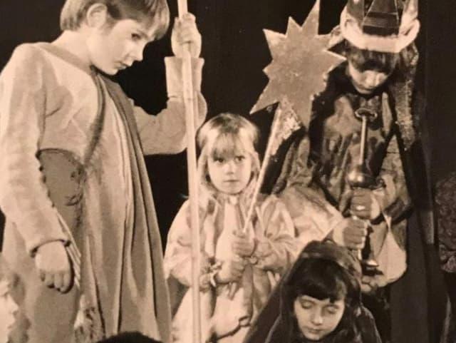 Kinder beim Krippenspiel. Ein blondes Mädchen hält einen Stern am einem Stab.