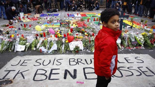Ein Junge steht auf einem Platz, auf dem unzählige Blumensträusse und Kerzen liegen.
