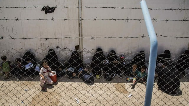 Frauen im Ganzkörperschleier sitzen hinter Stacheldraht am Schatten, Kinder sind auch dabei.