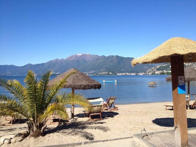 Palme auf Sandstrand, Liegestühle und Sonnenschirme aus Stroh. Ein See und Berge bei schönstem Sommerwetter.