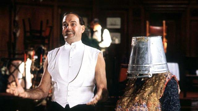 John Cleese, nur noch bekleidet mit weisser Weste und Fliege neben der Putzfrau, die das Erbrochene von Mr. Creosote aufputzen wollte.