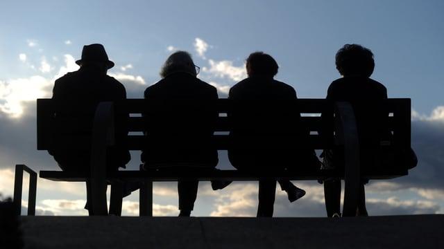 Vier Senioren sitzen auf einer Bank.