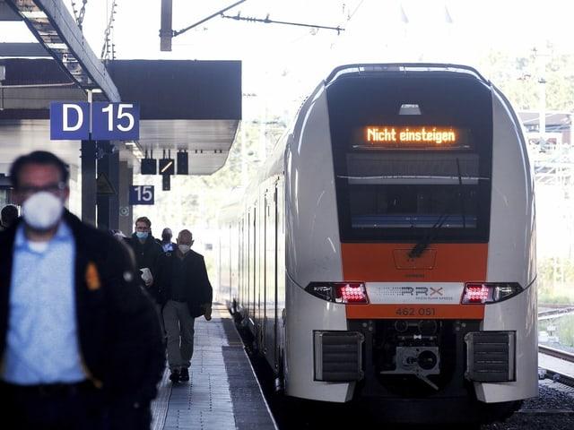 """Menschen stehen auf dem Gleis vor einem Zug mit der Aufschrift """"Nicht einsteigen"""""""