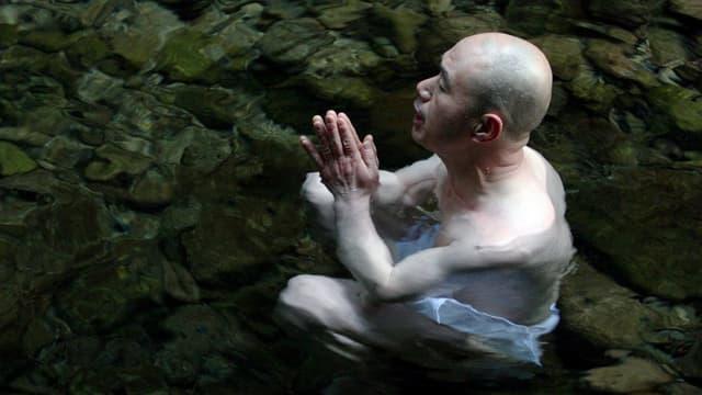 Ein Mönch meditiert im Wasser.