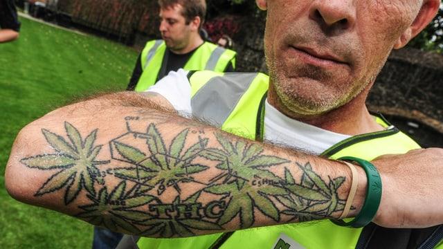 Ein Mann zeigt seinen mit Cannabis-Blättern tätöwierten Arm