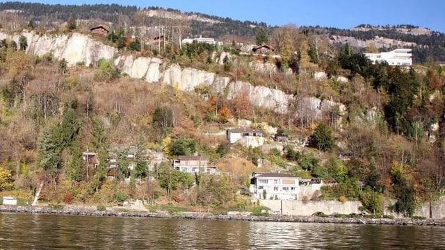 Blick vom Vierwaldstättersee auf ein Felsband. Darunter stehen mehrere Häuser.