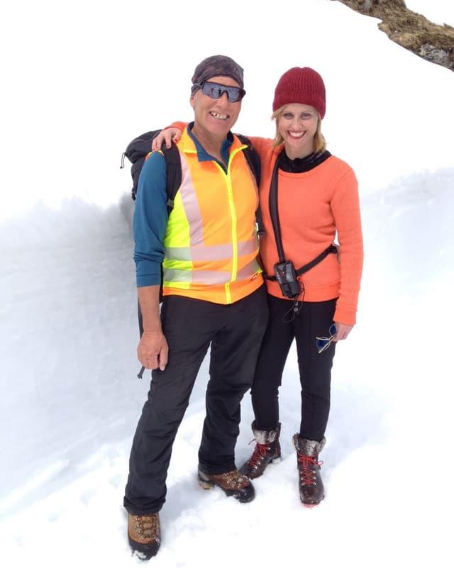 Sabine steht mit orangem Pullover und Lawinensuchgerät fröhlich neben einem lachenden Mann mit Leuchtweste und Rucksack. Hinter den beiden ist eine hohe Schneemauer zu sehen..