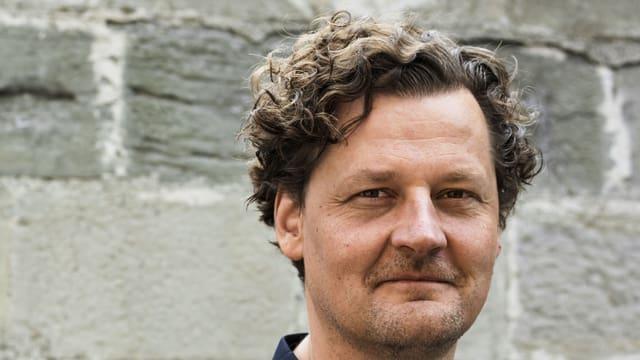 Ein Mann mit hellbraunen Locken vor einer grauen Mauer.