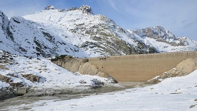 Eine Staumauer, davor eine Schnee- und Steinwüste.