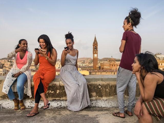 Junge Frauen auf einer Dachterasse. Sie schauen in ihre Smartphones.