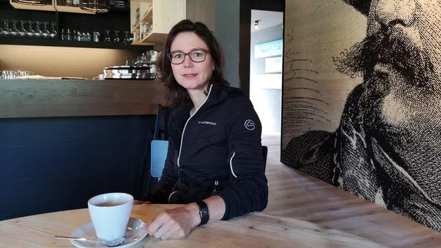 Frau in Restaurant vor Kaffeetasse.