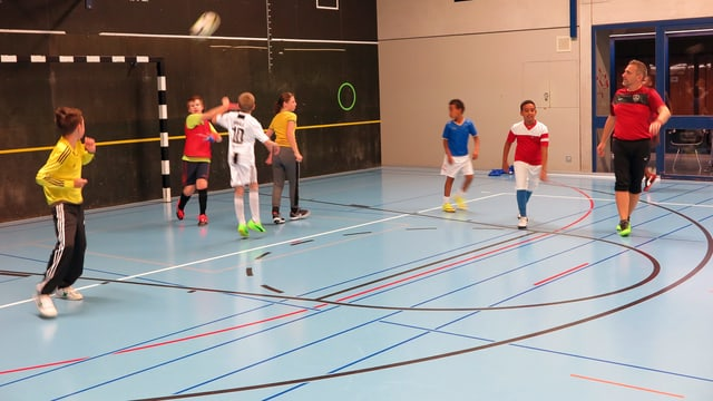 Sieben Kinder und ein Erwachsener spielen Fussball. Der Goalie wirft gerade aus.