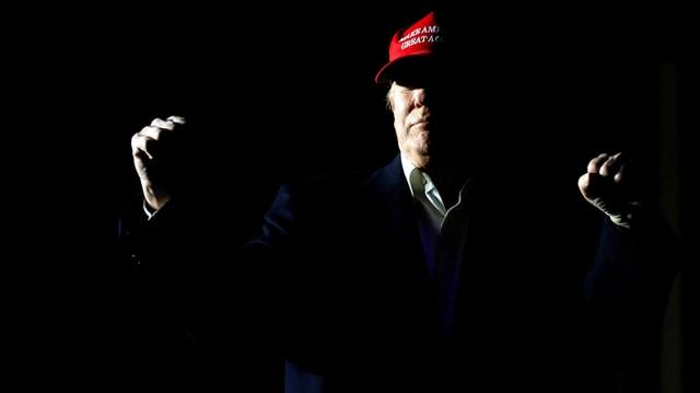 Donald Trump in Baseballmütze mit geballten Fäusten. Um ihn herum ist es dunkel.