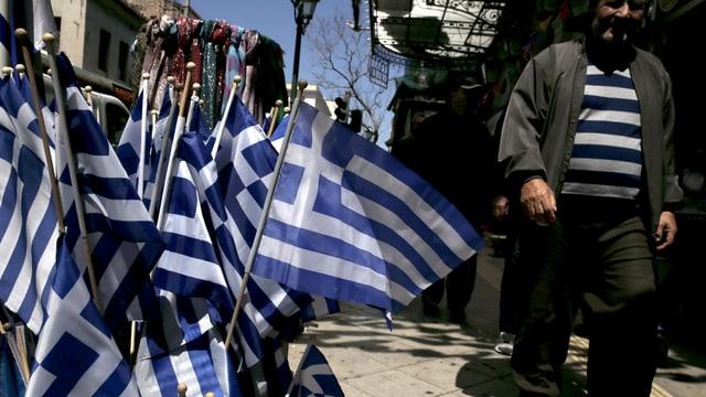 Symbolbild: Griechenland-Fähnchen vor einem Geschäft in Athen, daneben ein Passant mit blau-weiss-gestreiftem Sweatshirt.