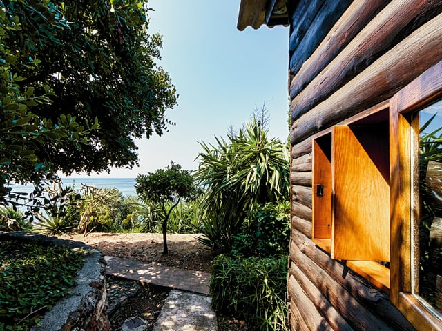 Hauswand aus Holz, daneben mediterraner Park und Sicht auf das Meer.
