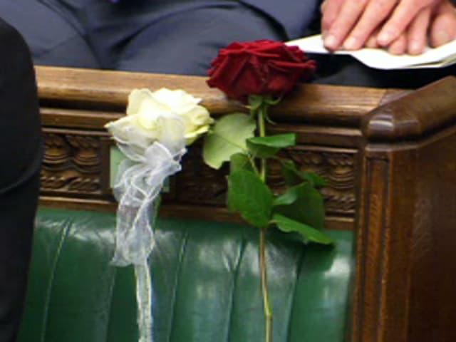 Zwei Rosen – eine weisse und eine rote – stecken am leeren Platz der ermordeten Abgeordneten Jo Cox.