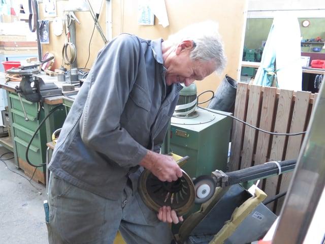 Jakob Schrämmli steht an einer Maschine und poliert einen Metalllüfter