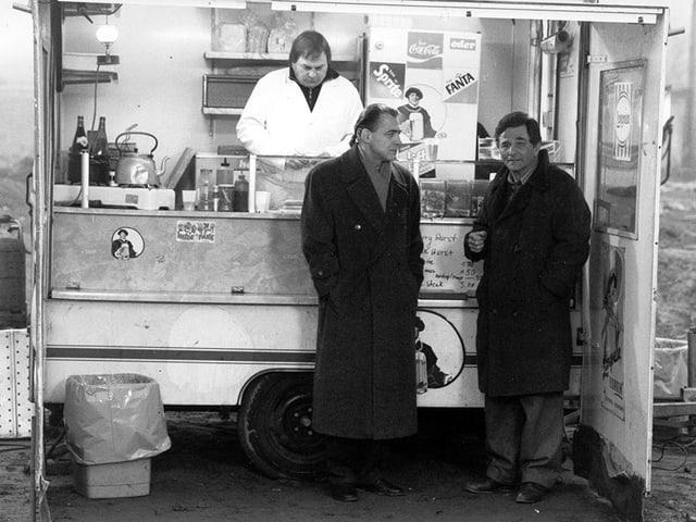 Schwarzweissbild: Zwei Männer in Mänteln stehen an einem Imbissstand