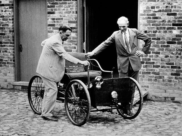 Ford (r.) mit dem ersten Auto, das er baute, auf einer Kopfsteinpflaster-Strasse vor einer Wand.