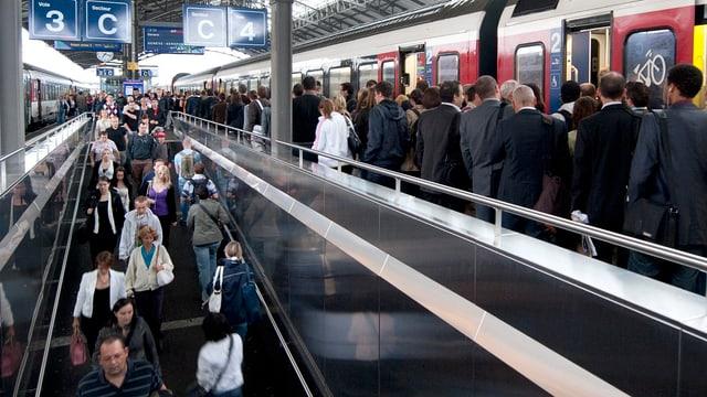 Menschen an einem Bahnhof.