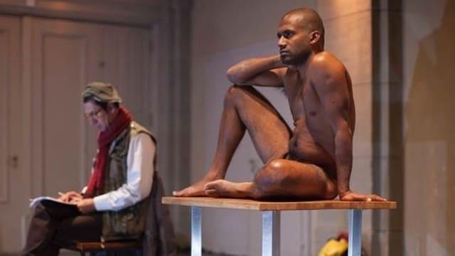 Theaterszene: Ein Mann mit rotem Schal sitzt auf einem Stuhl, ein dunkelhäutiger Mann nackt auf einem Tisch.