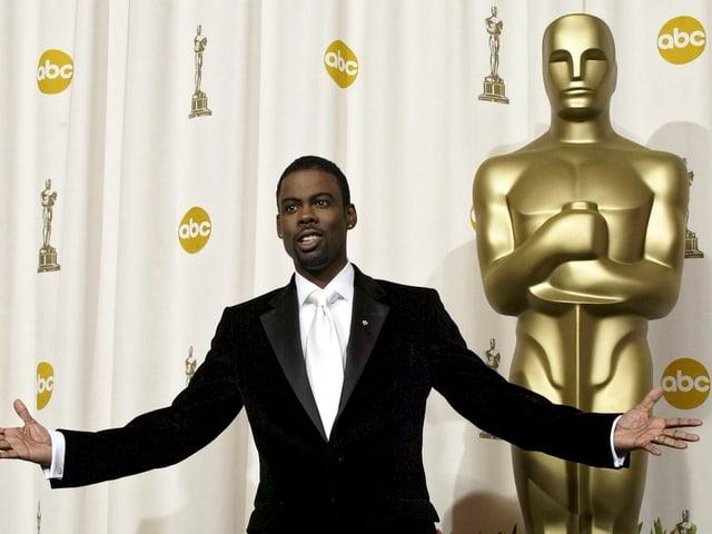Chris Rock die Arme ausgespreckt vor einer grossen Oscar-Statue stehend.