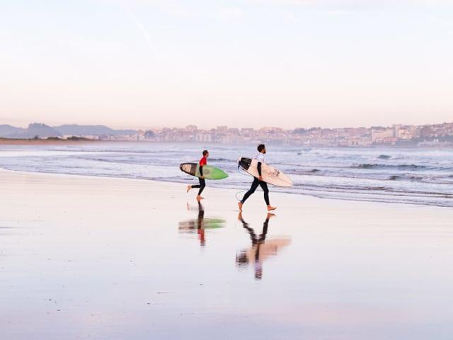 Surfer laufen ins Meer.