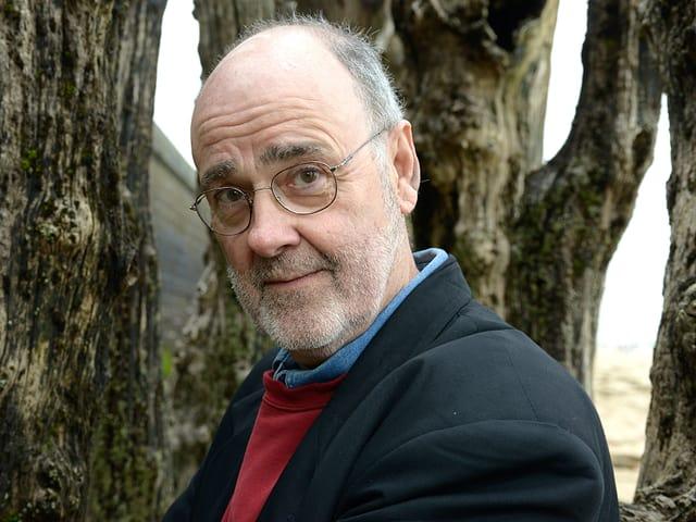 Der Autor James Sallis vor Bäumen.