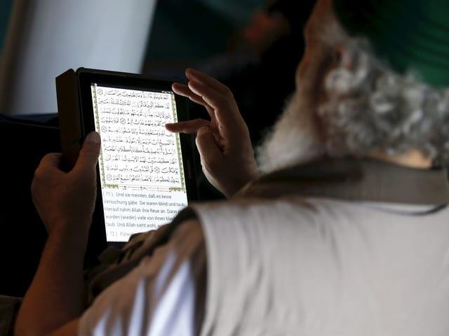 Ein Muslim liest den Koran auf einem Tablet.