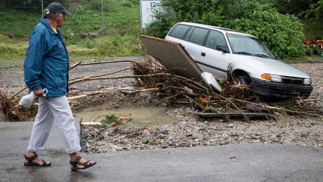Mann geht an einem beschädigten Auto vorbei.