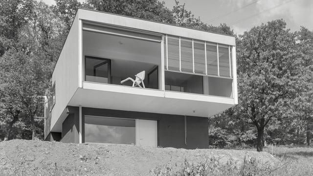 ein schwarz-weiss Foto von einem quadratischen Haus am Hang
