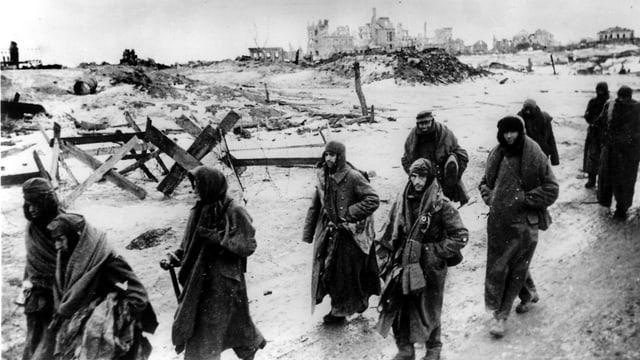 Gruppe von Soldaten in Mänteln läuft durch Trümmer.