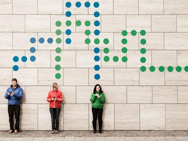 Drei junge Leute stehen an einer Wand und schauen jeweils auf ein Smartphone. Über ihren Köpfen sind gepunktete Linien zu sehen, die sie miteinander verbinden oder aus dem Bild hinausführen.