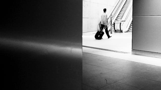 Ein Mann mit Rollkoffer in einem Bahnhof.